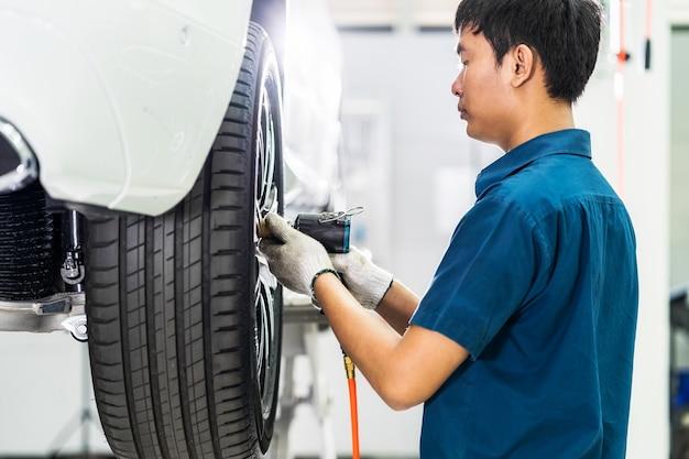 Meccanico asiatico che controlla e ripara le ruote dell'auto nel centro servizi di manutenzione