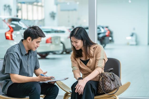 Meccanico asiatico che spiega la lista di controllo del servizio di manutenzione al cliente nello showroom