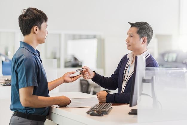 Meccanico asiatico che riceve la chiave automatica dell'auto per il controllo presso il centro servizi di manutenzione