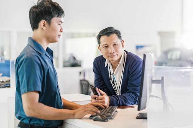 Meccanico asiatico che digita la tastiera quando serve il cliente per il controllo