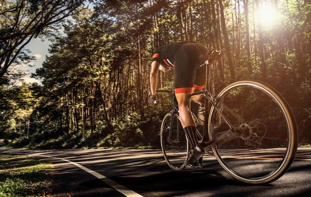 Gli uomini asiatici stanno pedalando in bici al mattino
