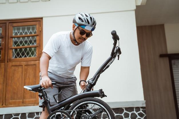 Gli occhiali da sole da uomo asiatici provano a piegare la bici pieghevole per prepararsi ad andare al lavoro