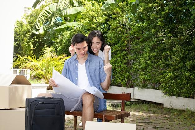 Coppie asiatiche di uomini e donne in possesso di un foglio di carta progetti per la costruzione di una nuova casa sono felici di costruire una famiglia insieme. concetto di iniziare una vita coniugale costruisci una famiglia felice.