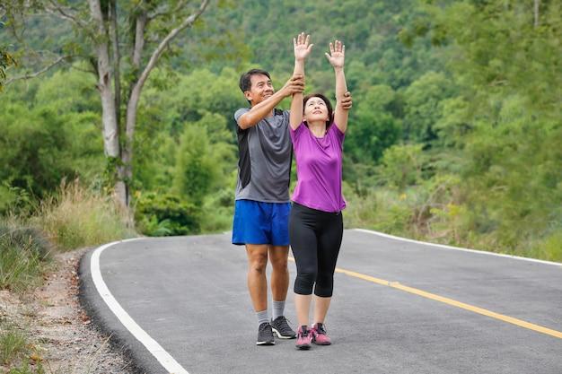 Coppia asiatica di mezza età che allunga i muscoli prima di fare jogging nel parco