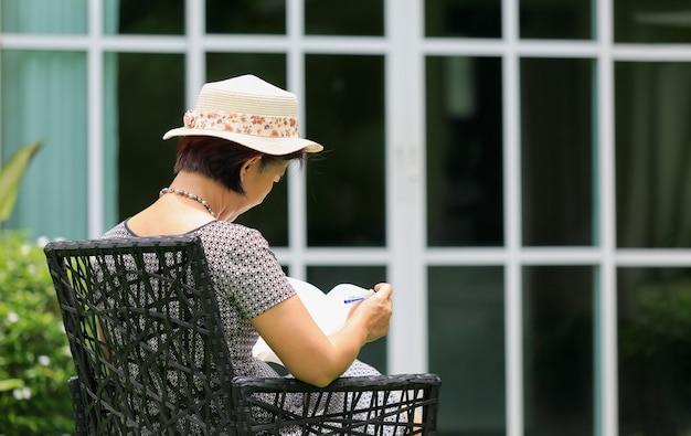 La donna asiatica di mezza età seduta si rilassa nel cortile