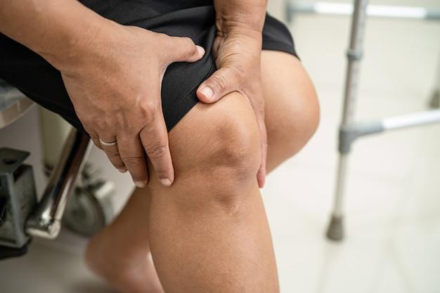 Il paziente asiatico di mezza età della donna tocca e sente dolore al ginocchio, concetto medico sano.