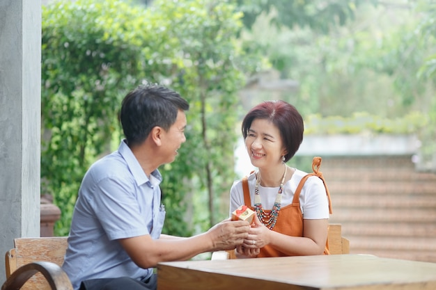 L'uomo di mezza età asiatico dà un regalo a sua moglie nel giorno del matrimonio di anniversario
