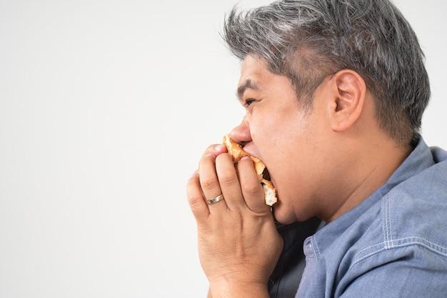 L'uomo di mezza età asiatico tiene e mangia un hamburger deliziosamente