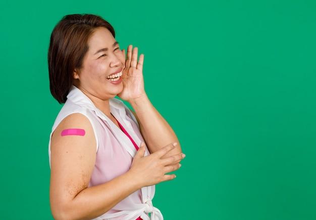 Donna asiatica di mezza età che ride con sollievo, il braccio con una benda che mostra che è stata vaccinata per il virus covid 19 su sfondo verde. concetto per la vaccinazione contro il covid 19.