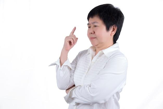 Donna asiatica di mezza età in camicia bianca che punta il dito, pensando isolato su sfondo bianco