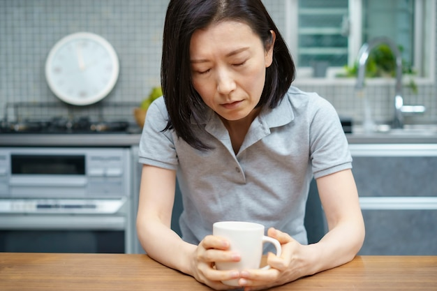 Donna di mezza età asiatica con uno sguardo stanco nella stanza