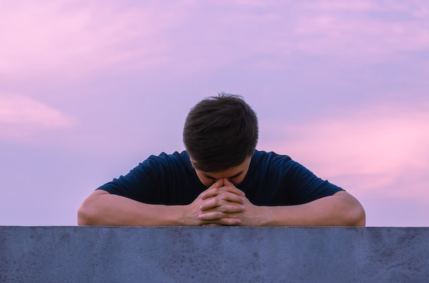 L'uomo depresso miserabile asiatico rimane solo con lo sfondo del cielo