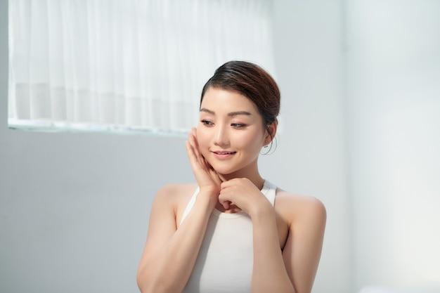 Ritratto di modello asiatico. la giovane donna con tocca il viso contro il bianco
