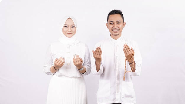 Le coppie asiatiche del molem pregano lo spazio bianco isolato