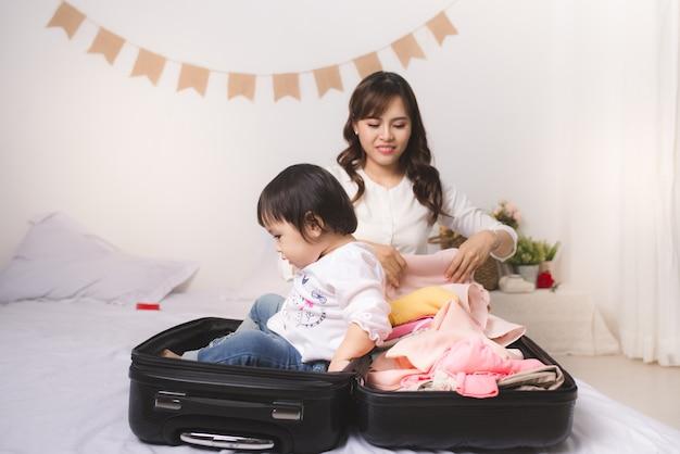 Mamma e bambina asiatiche con bagaglio in valigia e vestiti pronti per viaggiare in vacanza