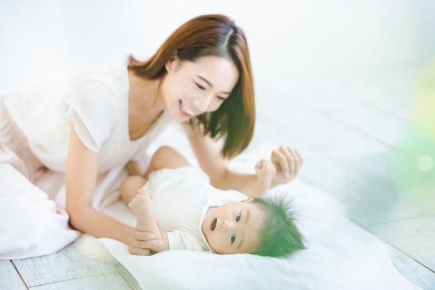 Mamma asiatica e bambino che giocano in casa