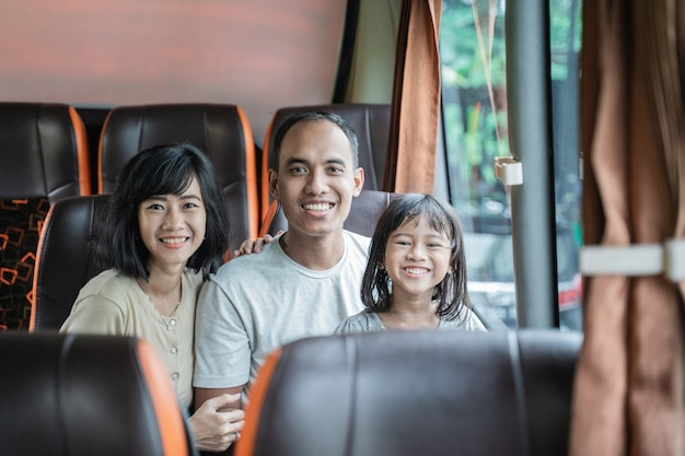Mamma e papà asiatici sorridono alla telecamera mentre cullano la figlia mentre sono seduti sul sedile dell'autobus durante il viaggio