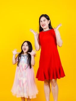 Mamma e figlia asiatiche che scattano foto ritratto insieme su sfondo giallo con divertenti e adorabili.