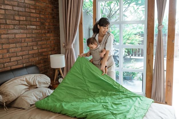 La mamma asiatica e il suo bambino puliscono e sistemano la coperta sul letto