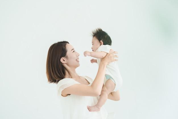 Mamma asiatica che tiene in braccio un bambino nella stanza luminosa