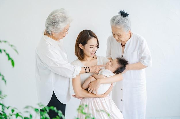 Mamma asiatica che tiene in braccio un bambino e due donne anziane