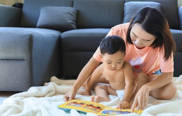 Libro di lettura asiatico della mamma con suo figlio