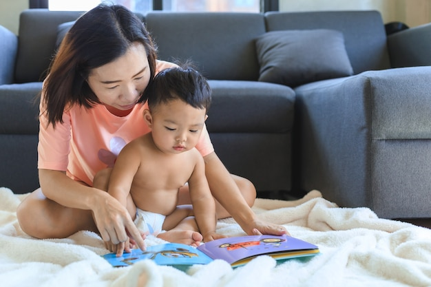 Mamma asiatica che insegna e legge il libro con il suo neonato sveglio a casa. concetto di famiglia e solidarietà