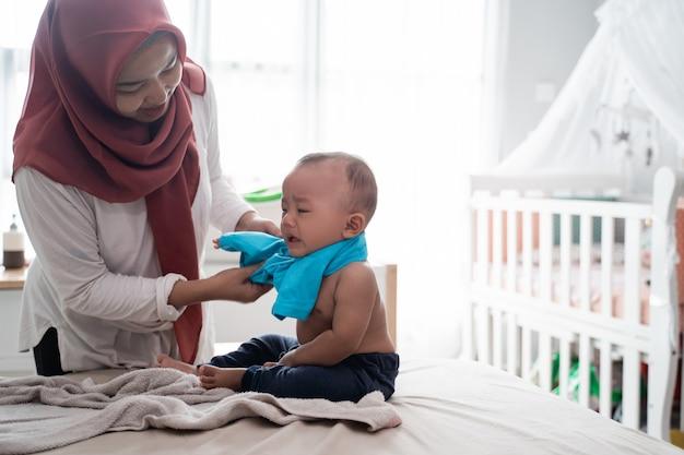 Madre asiatica che cambia i suoi vestiti del bambino