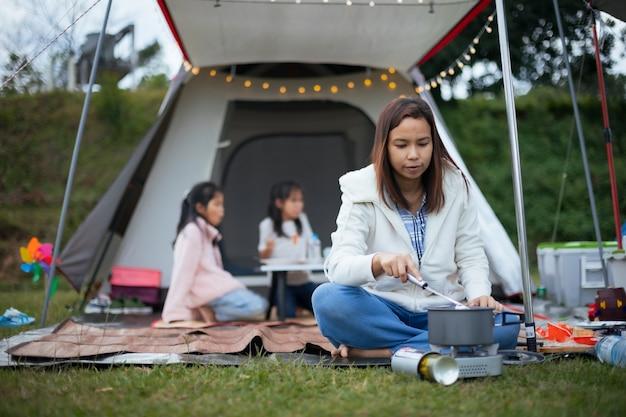 Madre asiatica che cucina per la famiglia fuori dalla tenda mentre si accampa con la famiglia nel campeggio con felicità.