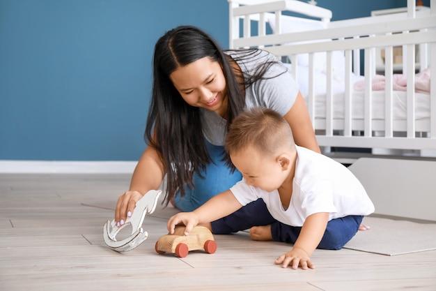 Madre asiatica e bambino carino che giocano a casa