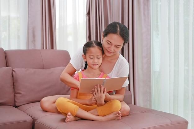 Madre e figlia asiatiche che leggono un libro sul divano. felice famiglia amorevole a casa