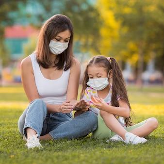 Madre asiatica e figlia che si siedono sull'erba mentre indossano maschere mediche
