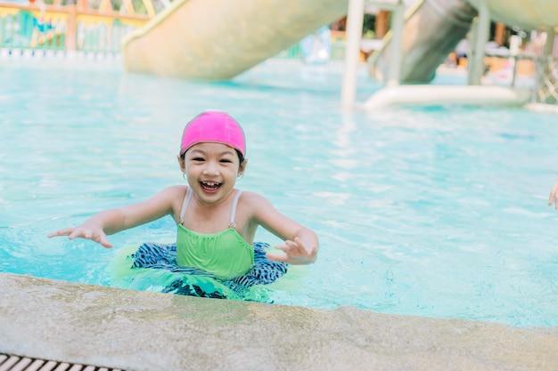 Madre e figlia asiatiche in piscina, parco acquatico. estate soleggiata.
