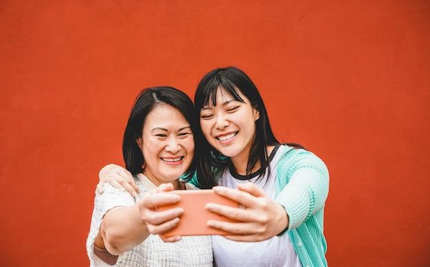 Madre asiatica e figlia che prendono selfie con lo smartphone per l'app di storia