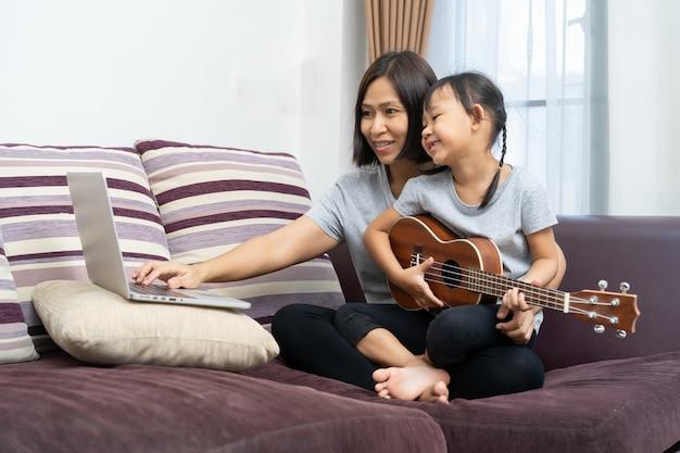 Madre e figlia asiatiche che per mezzo del computer portatile e delle ukulele a casa