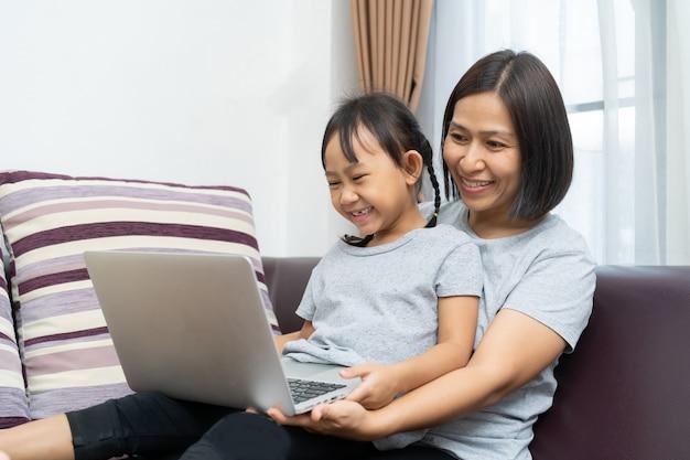 Madre e figlia asiatiche che per mezzo del computer portatile