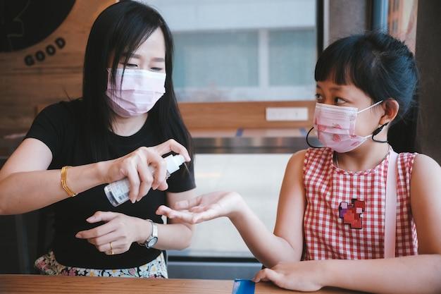 Madre asiatica e figlia che indossano una maschera utilizzando alcol spray per prevenire il covid-19
