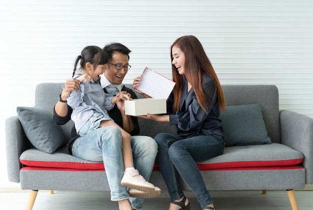 La madre e il padre asiatici fanno un regalo per la figlia. confezione regalo a sorpresa di concetto per buon compleanno.