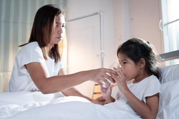 Madre asiatica che dà bicchiere d'acqua alla ragazza del bambino malato dopo aver mangiato la medicina in camera da letto