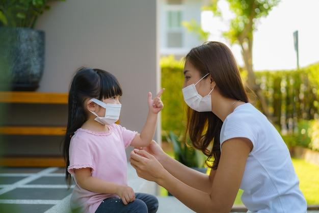 La madre asiatica aiuta sua figlia che indossa la maschera di protezione Foto Premium