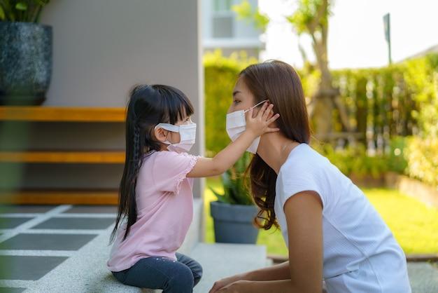 La madre asiatica aiuta sua figlia che indossa la maschera di protezione