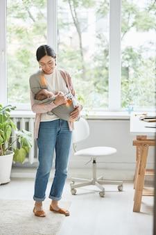 Madre asiatica che tiene in braccio il suo bambino addormentato che la guarda e sorride mentre sta in piedi nella stanza