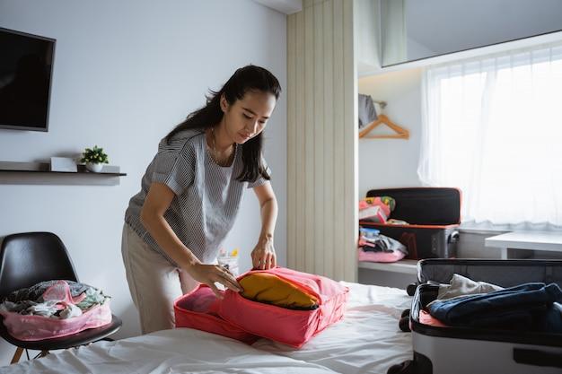 La madre asiatica prepara vestiti e borse