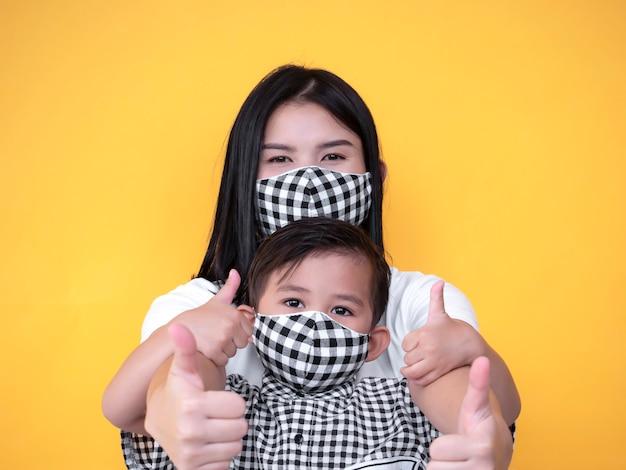 La madre e il figlio asiatici stanno mostrando il pollice su e la maschera d'uso
