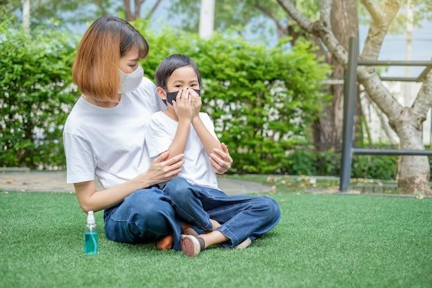 Madre asiatica e figlio indossano una maschera per proteggere il virus in giardino