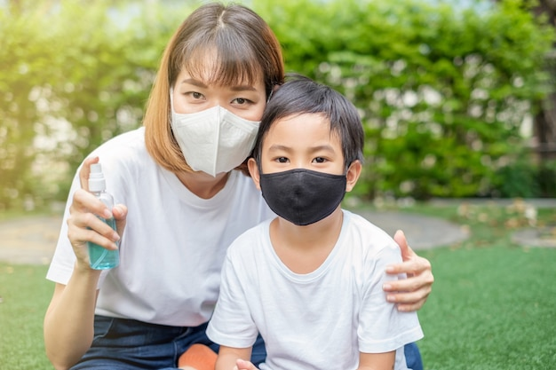 Madre asiatica e figlio che indossano una maschera per il viso e che tengono il flacone spray di alcol per proteggersi dal virus nel giardino di casa