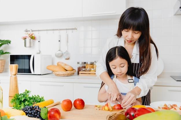 Madre asiatica che insegna al suo bambino usando il coltello per affettare la mela per cucinare il cibo in cucina.