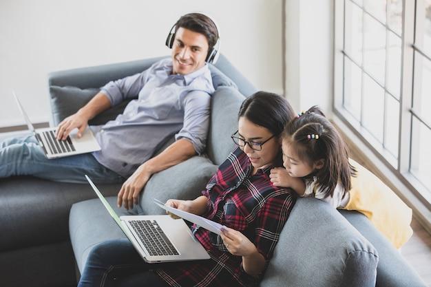 Madre asiatica che usa il computer portatile per lavorare sul divano in soggiorno mentre insegna e spiega la sua mezza piccola figlia carina. padre caucasico seduto e lavorando con il taccuino in sottofondo, famiglia felice.