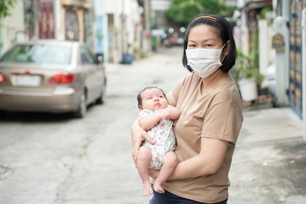 Madre asiatica che indossa la mascherina chirurgica che tiene il suo bambino, concetto di covid-19