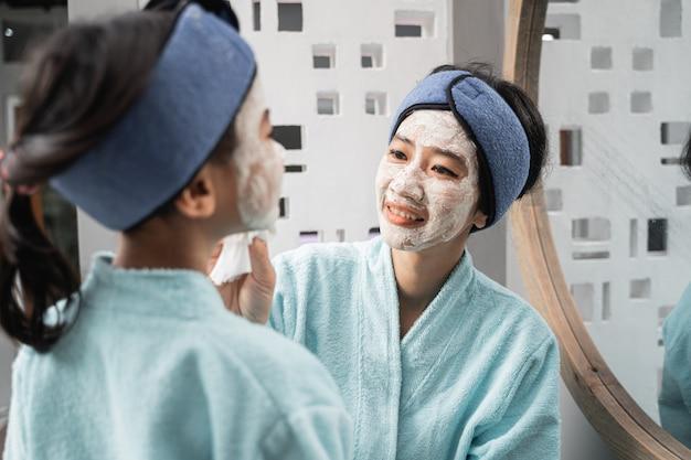 Anche la madre asiatica con una maschera color crema sul viso ha strofinato la maschera della sua bambina mentre indossava un asciugamano